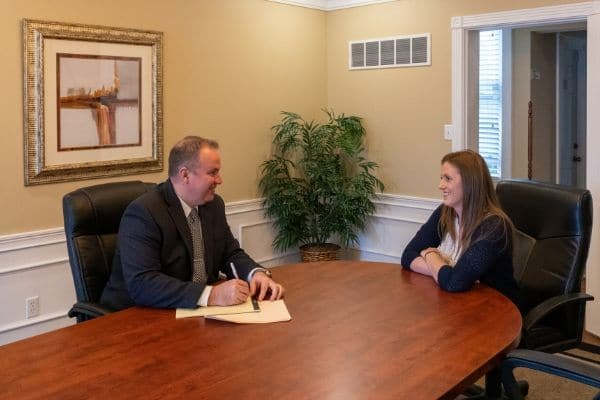 Christopher Jackson providing legal advice to a women in the conference room at his Northern KY headquarters..