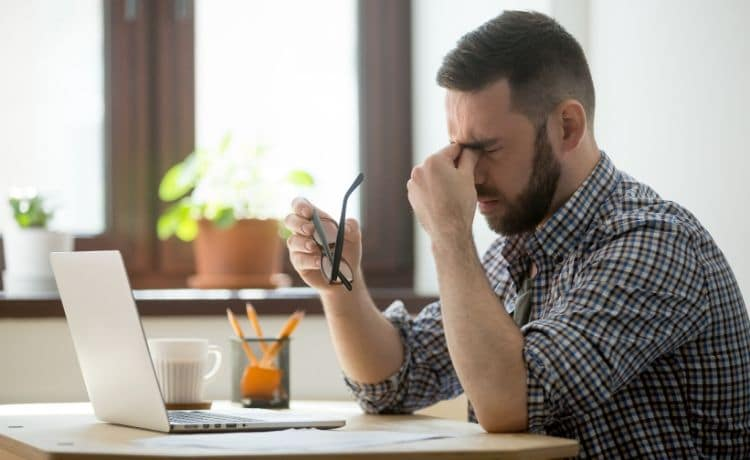 Man rubbing his eyes as he looks at computer.