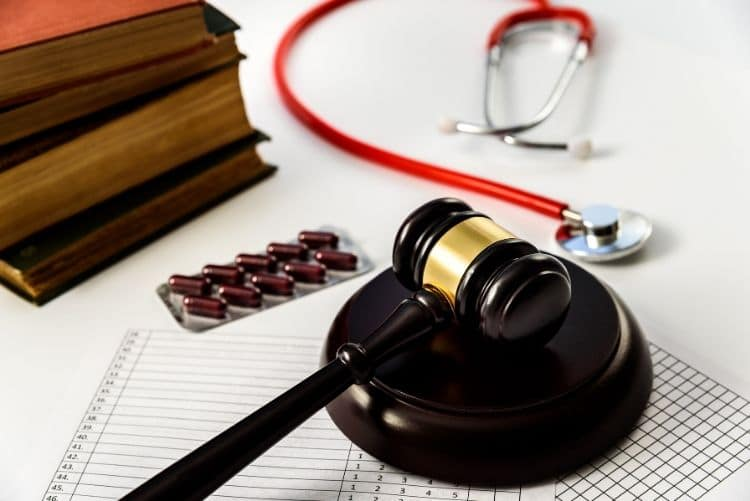 Gavel, law books, and a stethoscope on a desktop.